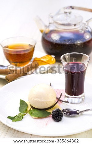 creamy dessert is decorated with blackberries on a white background