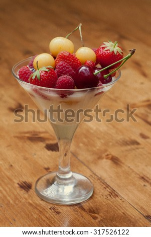 Creamy dessert with fresh summer fruits in cocktail glass. Yellow and red cherry, strawberry on top. Wooden background. soft focus. toned vintage paper texture! - stock photo