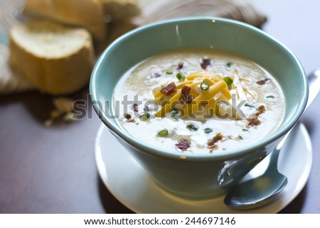 Creamy loaded baked potato soup with scallion garnished and fresh Italian bread - stock photo