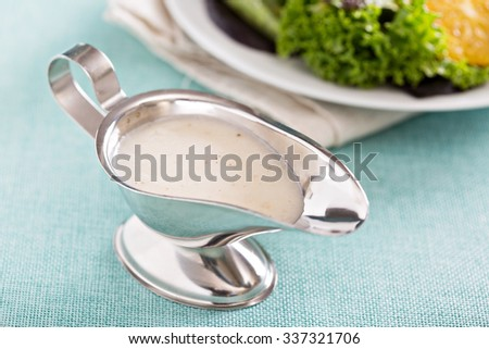 Creamy onion dressing in a small gravy dish - stock photo