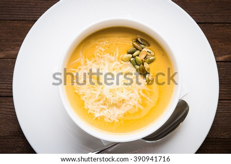Creamy pumpkin soup with sids and parmesan on dark wooden background top view. - stock photo