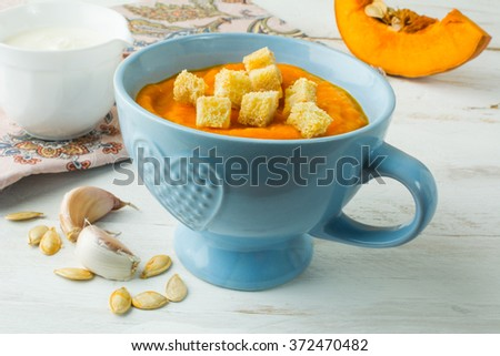 Creamy pumpkin squash vegetable soup with garlic croutons in a blue bowl and pumpkin slice on white wooden background. Pumpkin soup. Squash soup. Soup. Creamy soup. Vegetable soup  - stock photo
