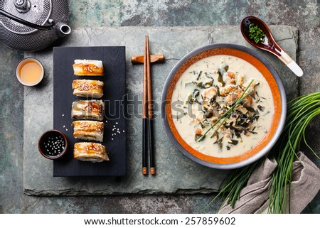 Creamy soup with Eel and sushi rolls on stone slate background - stock photo