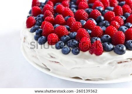 Creamy sweet cake with blueberries and raspberries - stock photo