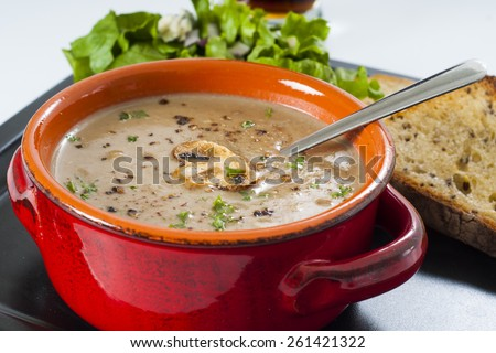 Creamy wild mushroom soup diner with garlic toast, lettuce salad, and a beer.