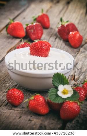 Creamy yogurt with strawberries, on wooden surface. - stock photo