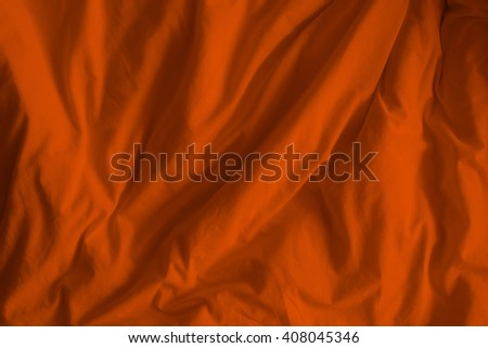 Creased orange cloth material fragment as a background. - stock photo