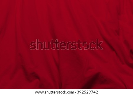 creased red cloth material fragment as a background. - stock photo