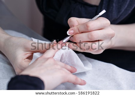 Creating a manicure, cuticle removal tool pusher shot closeup - stock photo