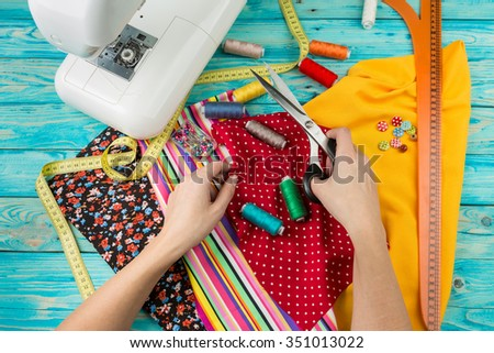 Creating a new fashion. Sewing Process - Women's hands behind her sewing.  Sewing machine with many sewing utensils on ablue wooden table. Top view.  - stock photo