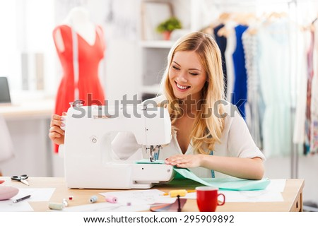 Creating new fashionable styles. Cheerful young woman sewing while sitting at her working place in fashion workshop  - stock photo