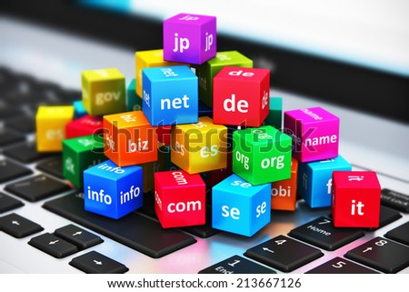 Creative abstract global internet communication PC technology and web telecommunication business computer concept: macro view of group of color cubes with domain names on laptop or notebook keyboard - stock photo