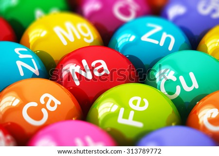 Creative abstract health lifestyle, diet and healthy eating and nutrition food concept: macro view of color balls, pills or tablets with minerals and microelements names with selective focus effect - stock photo
