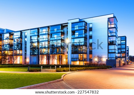 Creative abstract house building and city construction concept: evening outdoor urban view of modern real estate homes - stock photo