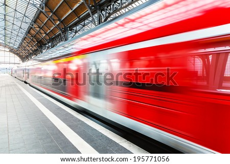Creative abstract railroad travel and railway transportation industrial concept: modern red high speed electric passenger commuter train at station platform with motion blur effect - stock photo
