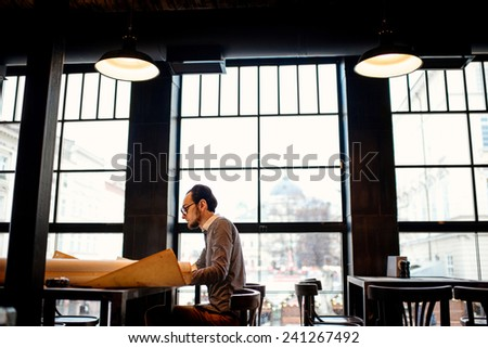 Creative architect projecting with pencil on the big drawings in the dark loft office or cafe. General plan with windows - stock photo