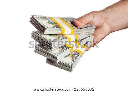 Creative business finance making money concept - hand holding stack of bundles of 100 US dollars 2013 edition banknotes (bills) isolated on white