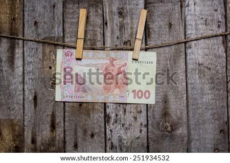 Creative business finance making money concept. Money on a clothespin on a wooden background . Ukrainian hrivna - stock photo