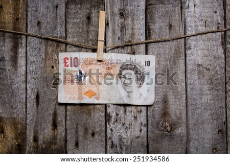 Creative business finance making money concept. Money on a clothespin on a wooden background. Pounds - stock photo