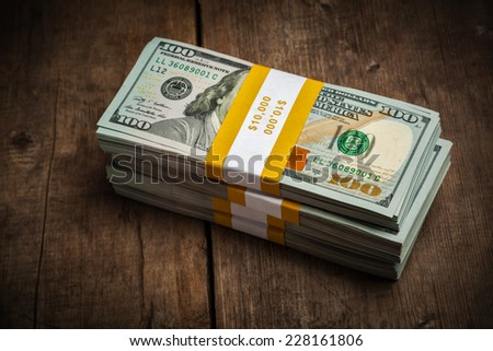 Creative business finance making money concept - stacks of new 100 US dollars 2013 edition banknotes (bills) bundles isolated on wooden background - stock photo