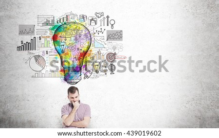 Creative business idea concept with thinking man standing against concrete wall with colorful light bulb sketch and business charts - stock photo