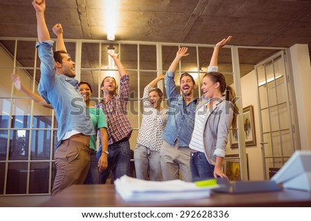 Creative business team waving their hands together at the office - stock photo