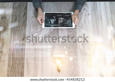 Creative business working.  Photo graphic designer hand working with design digital tablet and light bulb on wood table. Digital business strategy layer effect. View from top. Double exposure effects - stock photo