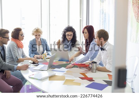 Creative businesspeople analyzing photographs at conference table in office - stock photo