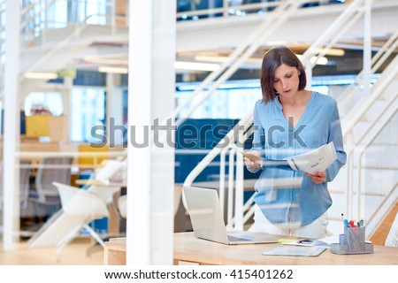 Creative businesswoman looking at paperwork in a modern office - stock photo