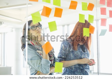 Creative businesswomen reading sticky notes on glass wall in office - stock photo