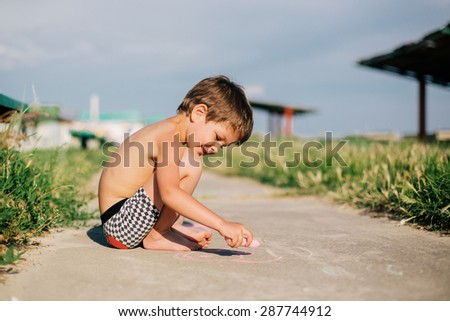Creative child. Little boy painting with colorful chalks outdoors in summer