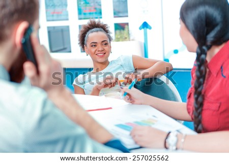 Creative colleagues. Rear view of young creative man talking over mobile phone while sitting with his international colleagues in the meeting room - stock photo