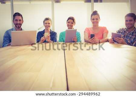 Creative colleagues with laptop and digital tablet smiling at camera in the office - stock photo