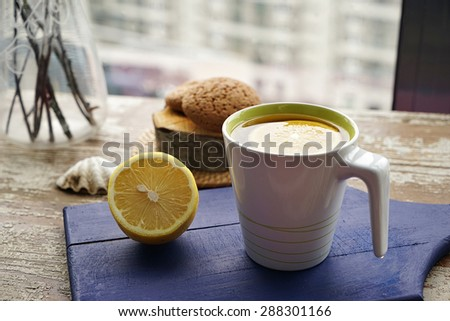 creative composition of lemon laying on the wooden surface and cup with hot tea - stock photo