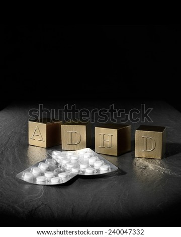 Creative concept image for Attention Deficit Hyperactivity Syndrome or ADHD. Gold wooden blocks and medication tablets against a black background. Copy space. - stock photo