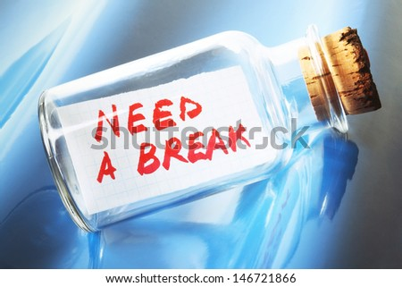 "Creative concept of a message in a bottle saying ""Need a break"" - stock photo"