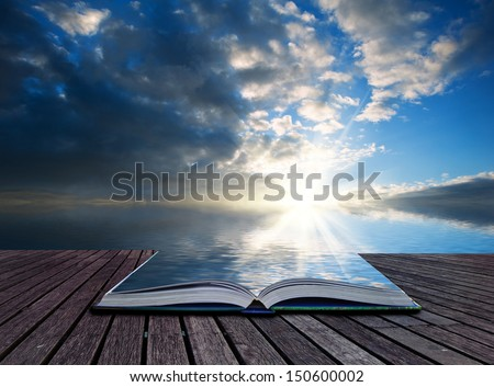 Creative concept pages of book Stunning landscape at sunset reflected in ocean - stock photo