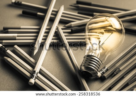 Creative content  writing, light bulb and many pencils on the table - stock photo