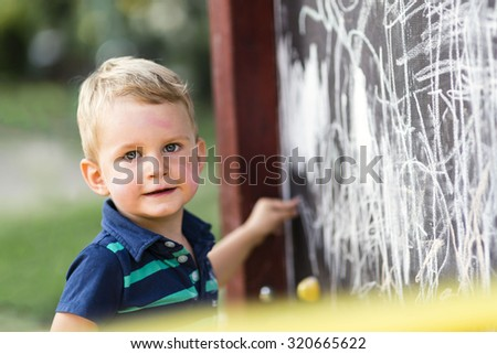 Creative cute toddler drawing with chalk outdoors