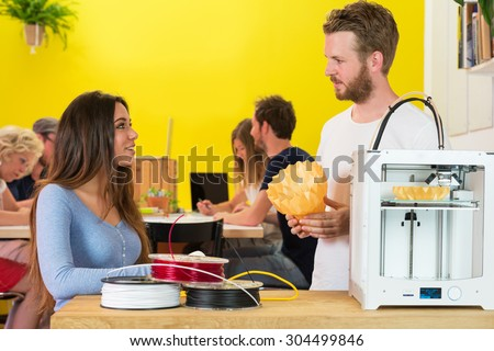 Creative 3D designers discussing over product at counter in printing studio - stock photo