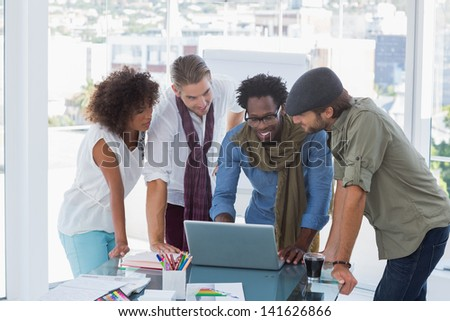 Creative designers working on a laptop in a bright modern office - stock photo