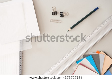 Creative Desktop from Above - pencil, paper sheets and pastel tones - stock photo
