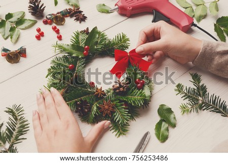 Creative diy craft hobby. Making handmade wreath. Woman's leisure, tools, glue gun and trinkets for holiday decorations on white wooden table with female hands. Present concept