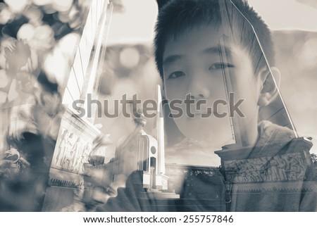 Creative double exposure portrait of boy in city - stock photo