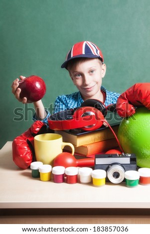 Creative education concept. Funny schoolboy sitting at table with colorful school accessories holding a big red apple smiling - stock photo