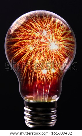 Creative Explosion as a fireworks display celebration represented by exploding sparks of color in the shape of a light bulb on black as a concept of innovation and creative power. - stock photo