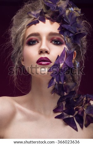 Creative fashionable image, the girl with a bright make-up and purple plant on the face. Picture taken in the studio.