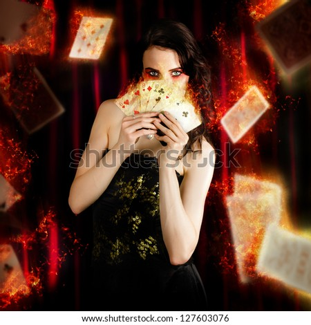 Creative Fine Art Photo Of A Beautiful Mystic Magician Holding Flaming Cards In A Depiction Of Tarot Fortune Telling - stock photo