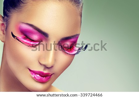 Creative Holiday Makeup with False long purple eyelashes closeup. Beauty model woman face make-up with fantasy bright eyelashes, perfect smooth skin and pink lipstick