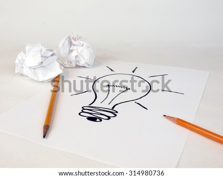 creative idea concept for business and intellectual layouts featuring an idea lightbulb with crumbled paper and pencils